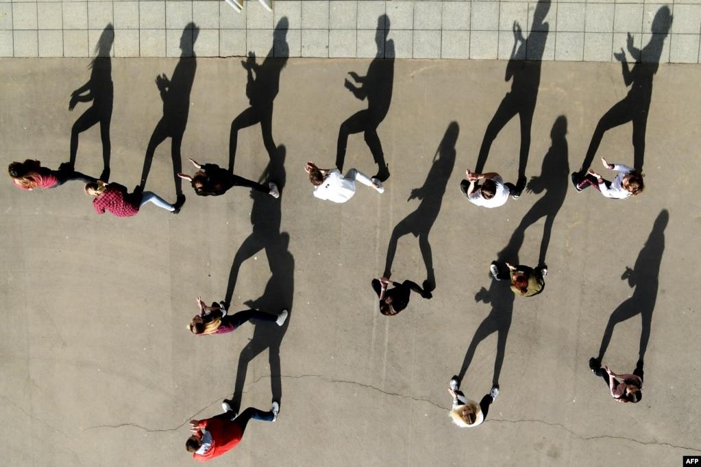 햇빛이 쨍쨍한 날 러시아 모스크바의 강 둑 위에서 학생들이 춤을 추고 있다.