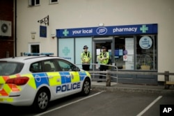 British police officers stand guard outside a branch of the Boots pharmacy in Amesbury, England, July 4, 2018.