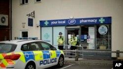 Des policiers britanniques montent la garde devant une succursale de la pharmacie Boots à Amesbury, en Angleterre, le 4 juillet 2018.