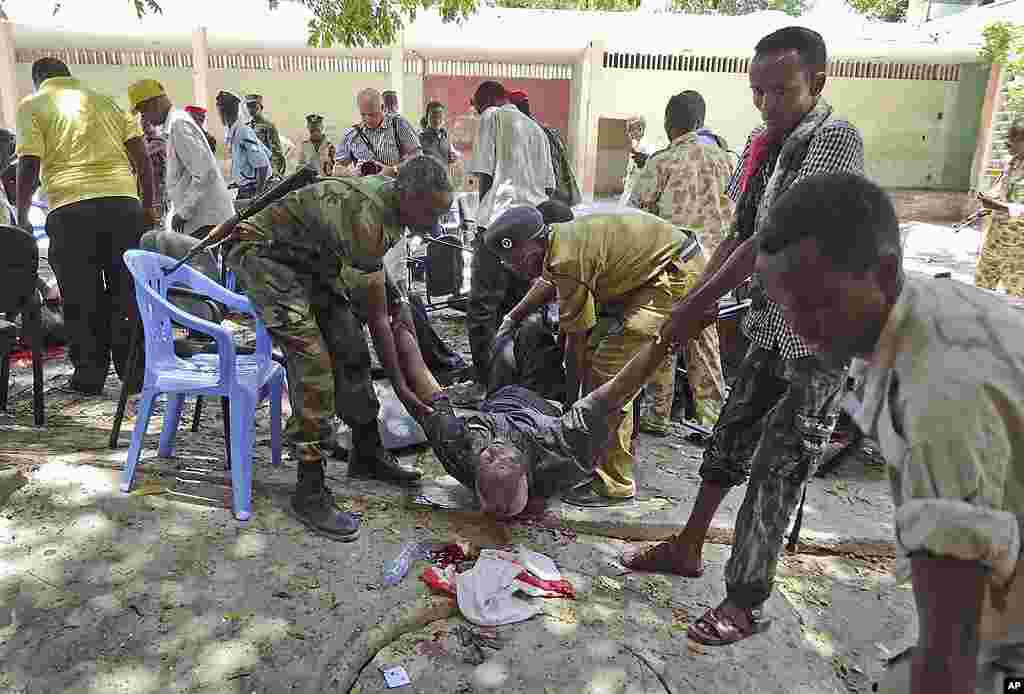 Somalis help a man wounded in a blast at the national theater. (AP)