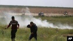 Manaifestantes palestinos huyen de gases lacrimógenos usados por soldados israelíes durante manifestaciones cerca de la frontera entre la Franja de Gaza e Israel, el viernes, 30 de marzo, de 2018.