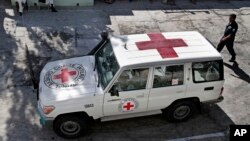 FILE - An Afghan policeman walks past a Red Cross vehicle in Jalalabad, east of Kabul, Afghanistan, May 30, 2013.