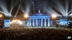 """FILE - Balloons of the art installation """"Lichtgrenze 2014"""" fly away in front of Brandenburg Gate during the central event commemorating the fall of the Wall in Berlin, Germany, Nov. 9, 2014."""