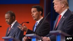 FILE - Candidates Donald Trump (R), Ben Carson (L) and Scott Walker (C) are seen participating in the first Republican presidential debate in Cleveland, Ohio, Aug. 6, 2015.