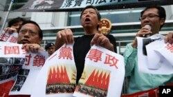 2012年11月8日,香港民主派活動人士在中聯辦前示威﹐並撕開印有一黨專政的海報。