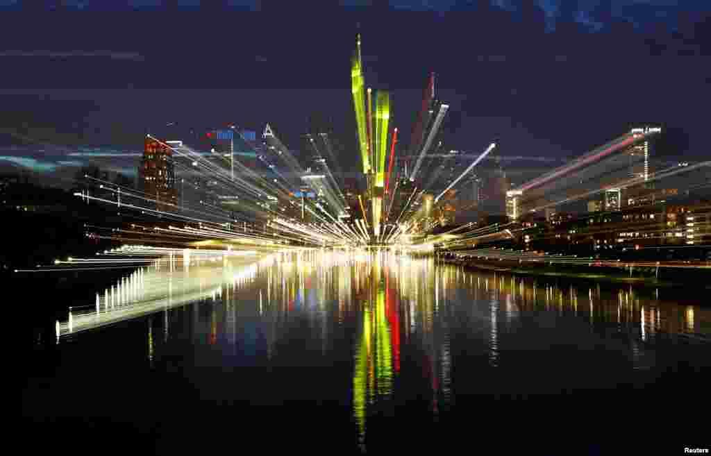 Bayangan gedung-gedung pencakar langit kota Frankfurt yang bercahaya terlihat di permukaan sungai Main di Frankfurt, Jerman.