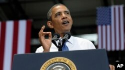 President Barack Obama gestures as he speaks at the Amazon fulfillment center in Chattanooga, Tennessee, July 30, 2013.