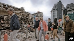 People walk through debris in the aftermath of a 6.3 magnitude earthquake in Christchurch, New Zealand, on February 22, 2011.