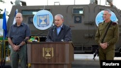 Israeli Prime Minister Benjamin Netanyahu (C) is flanked by Defense Minister Moshe Ya'alon (L) and Lieutenant-General Benny Gantz as he delivers a statement regarding an operation to locate three missing Israeli teenagers, at a military base near the West Bank Jewish settlement of Beit Haggai, near Hebron, June 19, 2014.