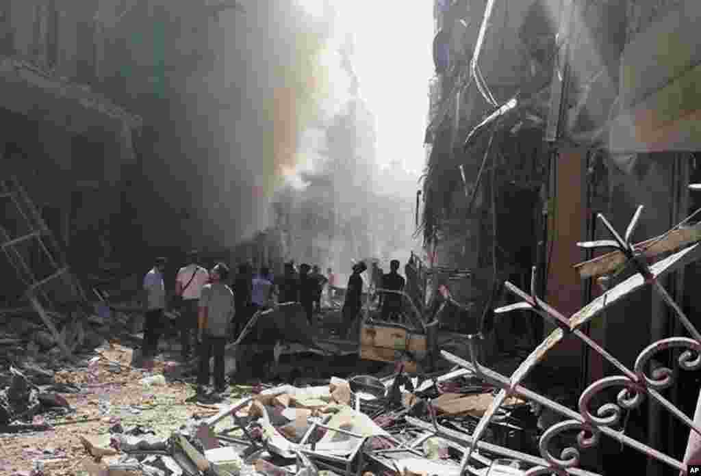 This photo provided by the activist group Syrian Observatory for Human Rights shows men and rubble after a Syrian government airstrike in Karm al-Jabal, Aleppo, Syria, June 26, 2014.