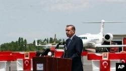 Turkish Prime Minister Recep Tayyip Erdogan delivers a speech near soldiers 'coffins at Van airport, eastern Turkey, 19 Jun 2010