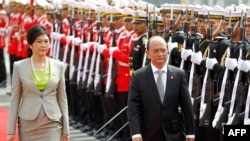 Burma President Thein Sein (R) and Thai Prime Minister Yingluck Shinawatra (L) review the honor guard during a welcoming ceremony in Bangkok, July 23, 2012.