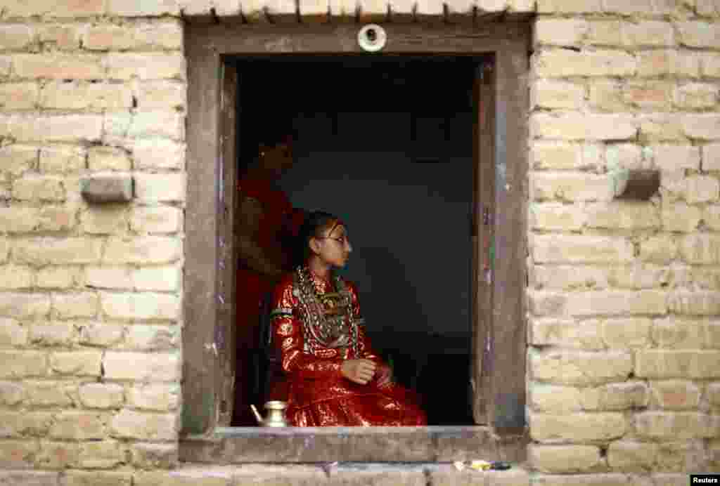 Living Goddess Kumari Samita Bajracharya is seen through a window of her house before she was taken to observe the Chariot Festival of Rato Machhindranath in Lalitpur, Nepal.