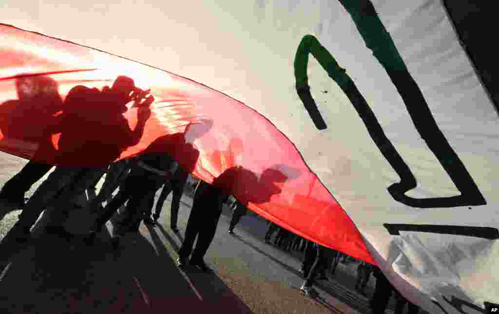 Iraqi protesters chant slogans as they wave national flags during a demonstration against corruption in Tahrir Square in Baghdad, Iraq.