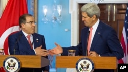 Secretary of State John Kerry, right, shakes hands with Tunisia Foreign Minister Mongi Hamdi, Monday, Aug. 4, 2014, during the US Africa Summit.