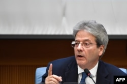 FILE - Italian Prime Minister Paolo Gentiloni gestures as he answers questions from journalists in Rome, Dec. 28, 2017.
