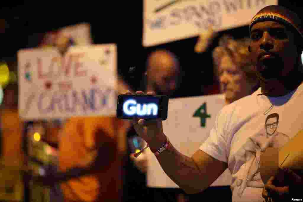 Um homem usa o seu telemóvel para passar uma mensagem sobre armas durante uma vig~ilai de velas em West Hollywood, California, na sequência do ataque à discoteca Pulse em Orlando, no Domingo de madrugada. Junho 12, 2016.