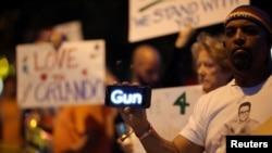 "Seorang pria memegang telepon genggam yang bertuliskan ""Gun"" saat pelaksanaan doa bersama di West Hollywood, California, untuk para korban serangan di klub gay Orlando, Florida (12/6)."