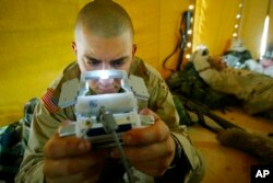 FILE - Pfc. Ralph Abbatiello of Long Island, New York, plays Pokemon while awaiting deployment at a camp in Kuwait, April 3, 2003.