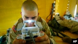 FILE - Pfc. Ralph Abbatiello of Long Island, New York, plays one of the latest versions of Pokemon while awaiting deployment at a camp in Kuwait, April 3, 2003.