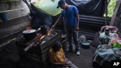 Pascuala Jonaj sits against a wood-burning stove as her son Victor Cal feeds the fire a day before he begins his trip to the United States, inside their home at the makeshift settlement Nuevo Queja, Guatemala, Thurs., July 8, 2021. (AP Photo/Rodrigo Abd)
