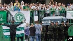 Anggota militer Brazil mengusung peti jenazah 19 anggota klub sepak bola Chapecoense yang tewas dalam kecelakaan di Kolombia, pada upacara pemakaman di stadion Chapeco, Brazil selatan (3/12).