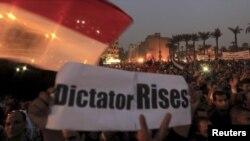 Para demonstran anti Presiden Morsi melakukan unjuk rasa di Lapangan Tahrir, Kairo sambil membawa spanduk yang menyamakan Morsi sebagai diktator (27/11).