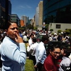Office workers stand outside a building after an earthquake, in Mexico City. March 20, 2012.