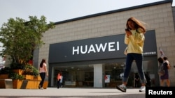 一名女子看着手机走过北京一家华为商店。(2019年5月16日)