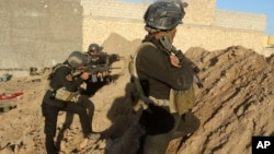FILE - Iraqi security forces take combat position at the front-line with Islamic State group militants as Iraqi Army and allied Sunni volunteer tribal fighters supported by U.S.-led coalition airstrikes are tightened the siege of Ramadi, Iraq, Nov. 30, 2015.