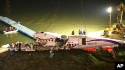 Badan pesawat TransAsia Airways ditarik ke bantaran sungai setelah jatuh di Taipei, Taiwan (4/2).