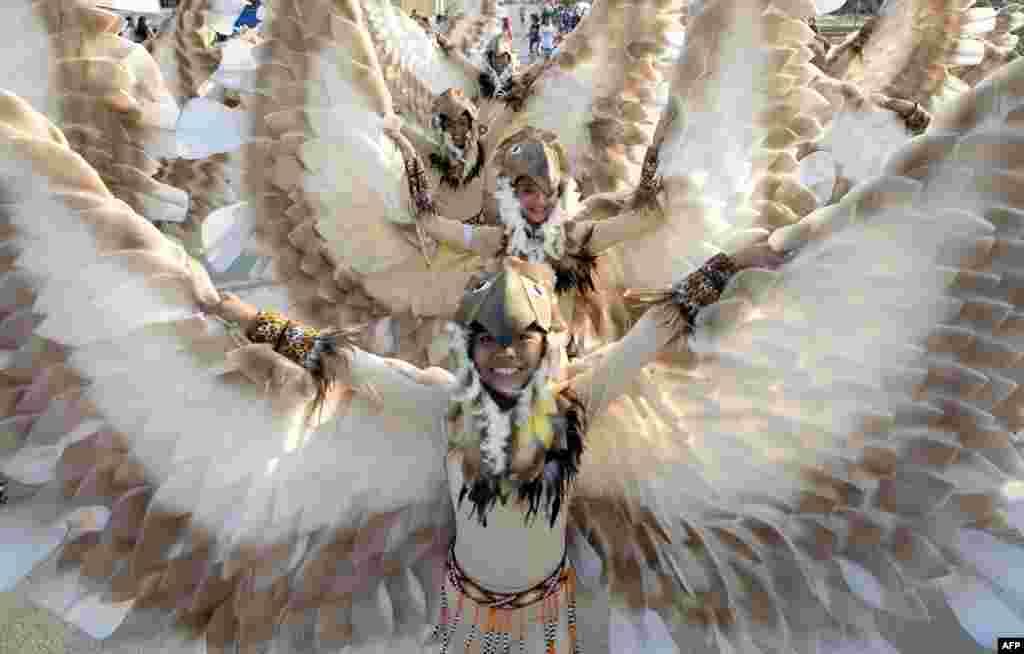 Para siswa mengenakan kostum burung menari dalam Festival Caracol tahunan di Manila, Filipina.