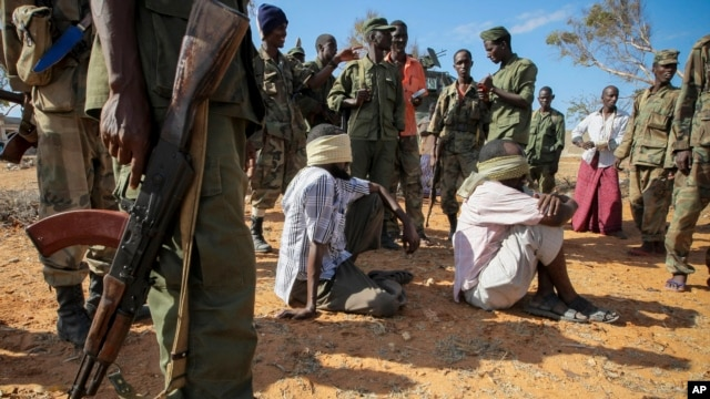 FILE - Alleged members of al-Shabab are blindfolded and guarded at a former police station by soldiers of the Somali National Army, in Kismayo, southern Somalia.
