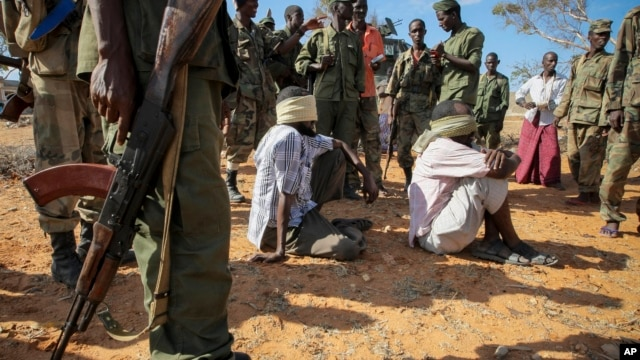 FILE - In this photo released by the African Union-United Nations Information Support Team, alleged al-Shabab members are blindfolded and guarded in Kismayo, southern Somalia on Oct. 3, 2012.