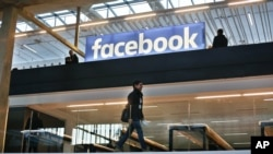 FILE - The Facebook logo is displayed in a startup companies gathering at Paris' Station F, Jan. 17, 2017.