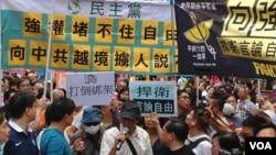 林榮基(持咪者)參加6月18日抗議遊行(美國之音海彥拍攝)