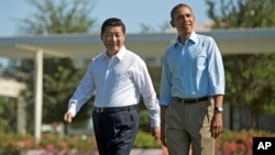 President Barack Obama and Chinese President Xi Jinping, left, walk at the Annenberg Retreat of the Sunnylands estate, in Rancho Mirage, California, June 8, 2013.