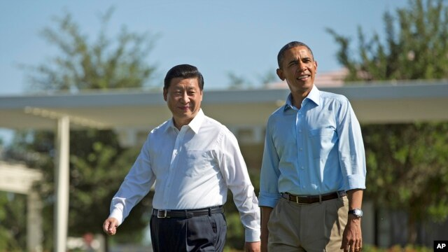 President Barack Obama and Chinese President Xi Jinping, left, walk at the Annenberg Retreat of the Sunnylands estate, June 8, 2013, in Rancho Mirage, Calif.