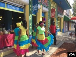 Creole dancers buy a fruit drink from a vendor at the Caribbean Marketplace in Little Haiti, Miami, Florida. (Photo: S. Lemaire / VOA)