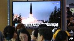 人们在韩国首尔一个地铁站的屏幕前看朝鲜导弹试射的新闻,2019年7月25日