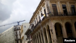 """FILE - A crane is seen behind an old building in Havana, Cuba, Sept. 18, 2015. As new construction is booming in Cuba, European businesses may view a tougher U.S. policy toward Havana as """"an opportunity for them to step in,"""" a Cuba expert says."""