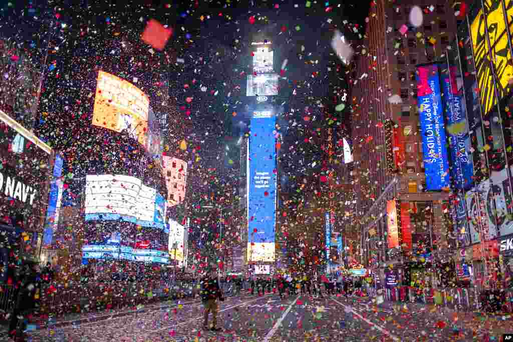 Confetti flies after the Times Square New Year's Eve Ball drops in a nearly empty Times Square, as the area normally packed with revelers remained closed off due to the ongoing coronavirus pandemic.