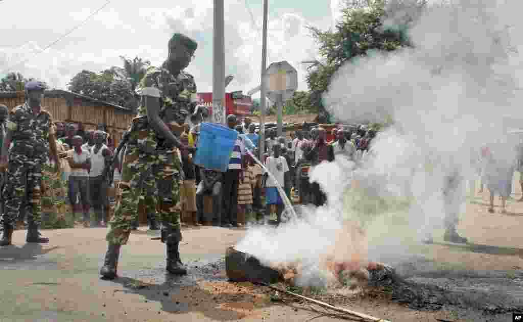 Un soldat de l'armée burundaise, avec un seau d'eau, tente d'éteindre le feu d'un pneu brulé par les manifestants dans la capitale Bujumbura, Burundi, lundi 27 avril 2015.
