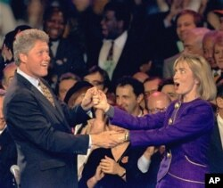 """Bill Clinton and Hillary Rodham Clinton dance on stage during a """"Get-Out-The-Vote"""" rally at the Brendan Byrne Arena in East Rutherford, N.J. Sunday night, Nov. 1, 1992. (AP Photo/Susan Ragan, File)"""