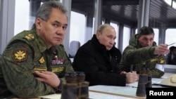 Владимир Путин и министр обороны России Сергей Шойгу (слева)