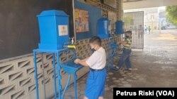 Siswa SD yang mengumpulkan tugas ke sekolah harus menjalani protokol kesehatan sebelum masuk sekolah. (Foto: VOA/Petrus Riski)