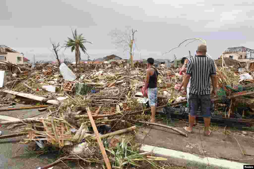 Watu walonusurika wakitathmini uharibifu kutokana na kimbunga kikubwa cha Haiyan kilichoharibu mji wa Tacloban katikati ya Ufilipino, Nov. 9, 2013.