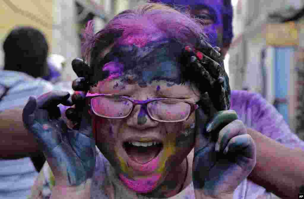 در مراسم فستيوال رنگها در کلکته، هند، يک توريست خارجی صورت توريست ديگری را با رنگ نقاشی میکند.