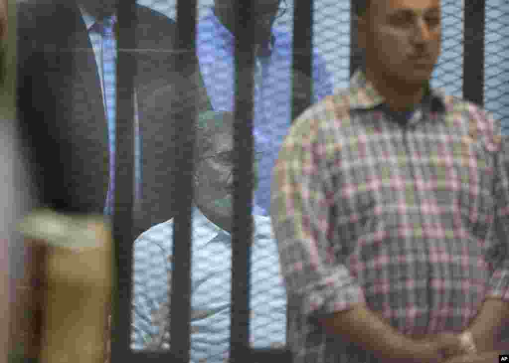 A plainclothes Egyptian policeman guards Egypt's ousted Islamist president Mohamed Morsi. Morsi is held in a soundproof glass cage within a makeshift courtroom at Egypt's national police academy in Cairo, April 21, 2015.