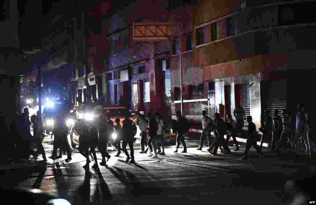 People cross a street in Caracas during a power outage on March 7, 2019 that left much of Venezuela in the dark early Thursday evening in what appeared to be one of the largest blackouts yet.